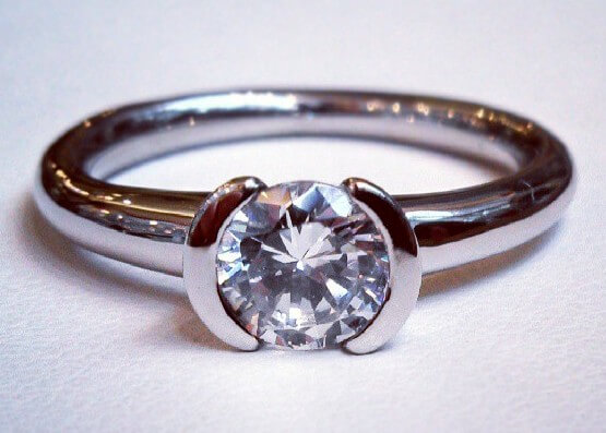 Partial bezel solitaire engagement ring in palladium