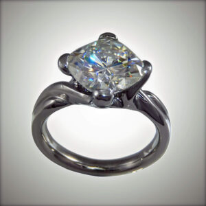 cushion cut moissanite in custom designed palladium engagement ring.